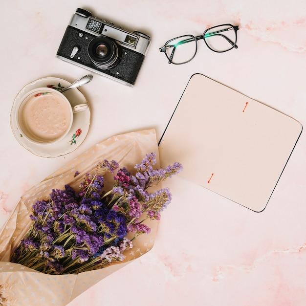 Leeg notitieboekje met koffiekop, camera en glazen op lijst Gratis Foto