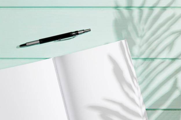 Leeg notitieboekje met pen en schaduwen Gratis Foto