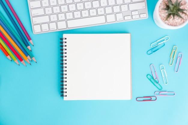 Leeg notitieboekje met toetsenbord en potlood op blauw Premium Foto