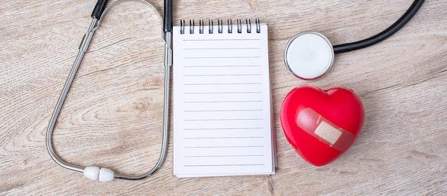 Leeg notitieboekje, stethoscoop met rode hartvorm op houten achtergrond. Premium Foto