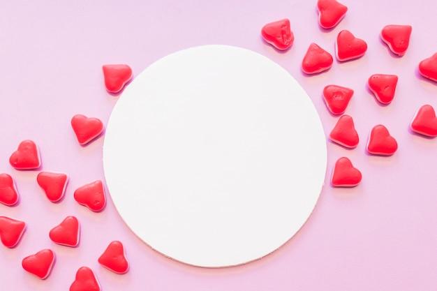 Leeg rond kader dat met het rode suikergoed van de hartvorm op roze achtergrond wordt verfraaid Gratis Foto