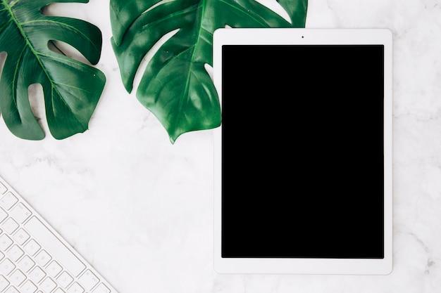 Leeg scherm digitale tablet met monstera bladeren en toetsenbord op witte marmeren bureau Gratis Foto