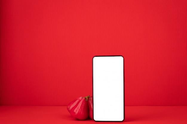 Leeg scherm op mobiele telefoon met rose apple fruit op rode achtergrond. Premium Foto