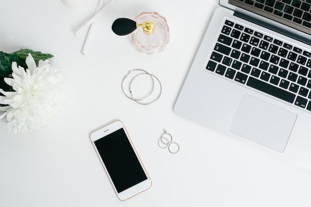 Leeg scherm telefoon en laptop toetsenbord op witte tafel met witte bloem Premium Foto