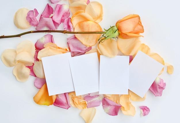 Leeg schrijfpapier met roze bloem en bloemblaadjes op witte achtergrond. Premium Foto