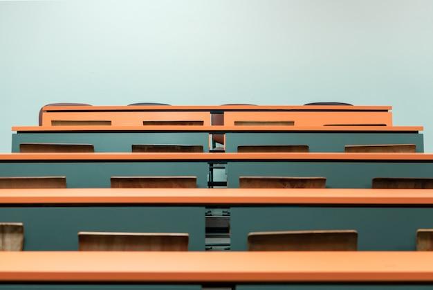 Leeg studentenbureau met houten stoel in het lezingsklaslokaal van universiteit Premium Foto