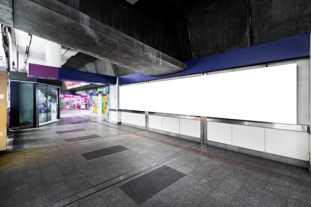 Leeg wit aanplakbord klaar voor nieuwe reclame voor klantinformatiediensten in openlucht bij skytrainstation Premium Foto