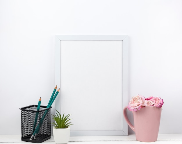 Leeg wit kader; potlood statief; bloemen en vetplant op tafel Gratis Foto