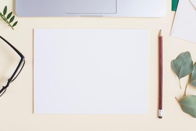 Leeg wit papier; potlood; bril; bladeren en laptop op beige achtergrond Gratis Foto