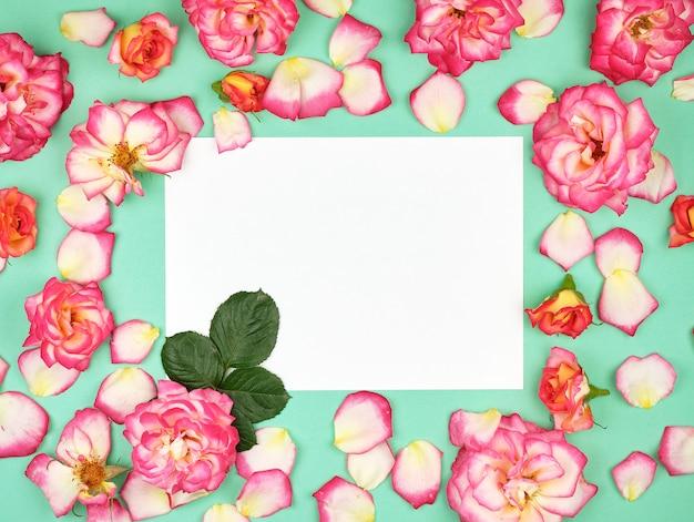 Leeg witboek blad en toppen van roze rozen Premium Foto