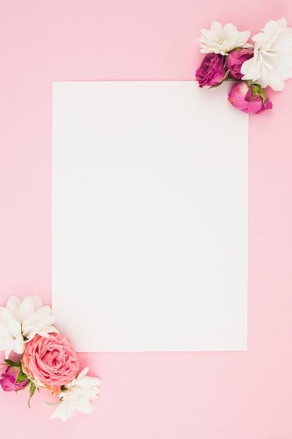 Leeg witboek met verse bloemen tegen roze achtergrond Gratis Foto