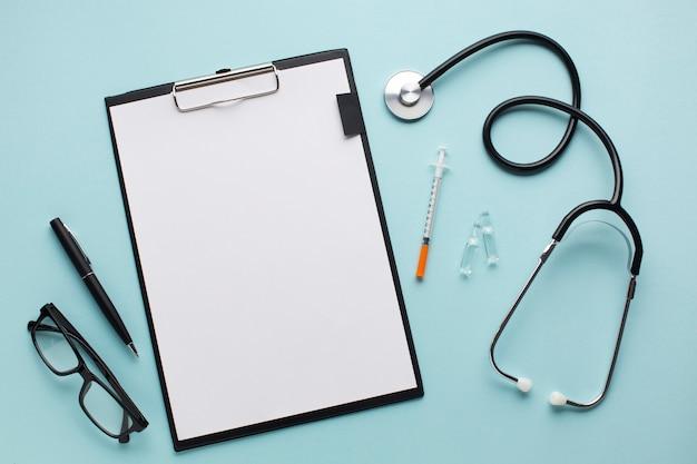 Leeg witboek op klembord dichtbij stethoscoop; injectie; pen en bril over blauw bureau Gratis Foto
