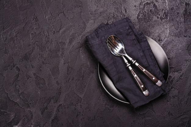 Leeg zwart plaat en tafelzilver op donkere steen backgroun. bovenaanzicht Premium Foto