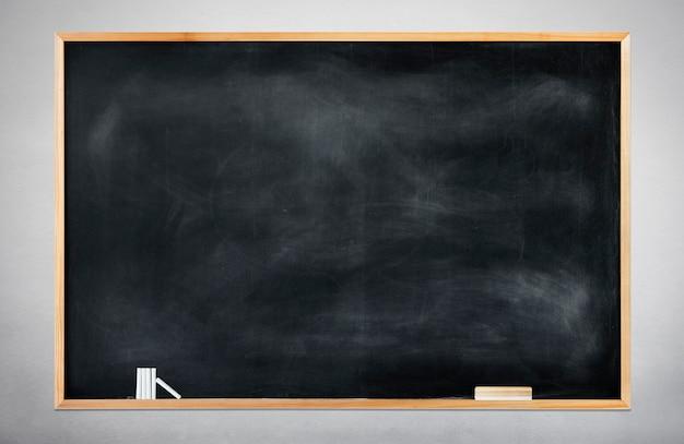 Leeg zwart schoolbord op een grijze achtergrond Gratis Foto