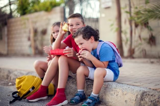 Leerlingen met een snack buiten. kinderen, onderwijs en voeding concept Premium Foto