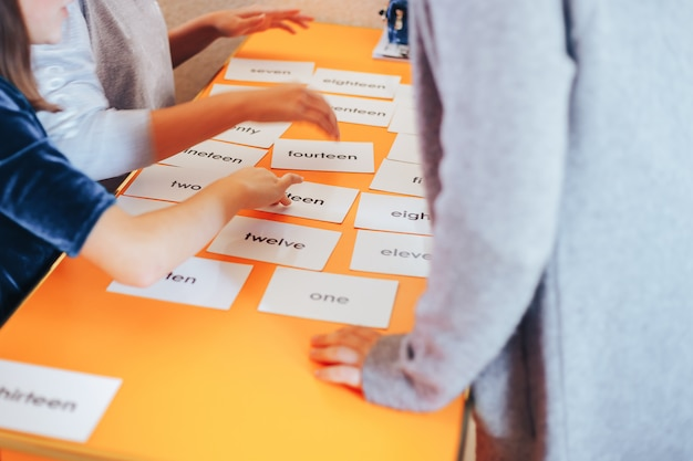 Leerlingen spelen kaarten met afbeeldingen in het engels en in de cijfers Premium Foto