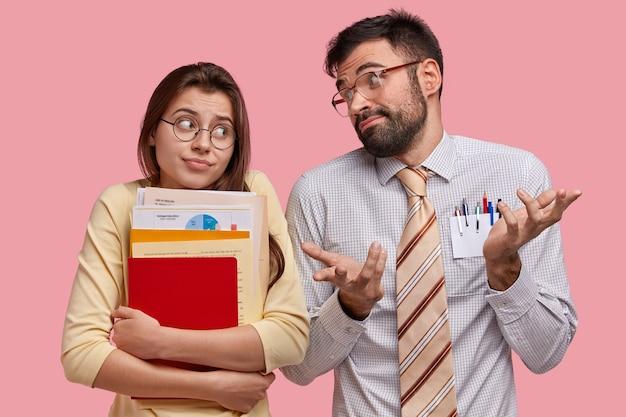 Leerlingen van de middelbare school hebben geen idee van uitdrukkingen, kijken elkaar twijfelend aan, kunnen niet beslissen over welk onderwerp ze cursuspapier moeten voorbereiden, staan naast elkaar Gratis Foto