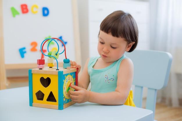 Leertijd van een kind met een houten klok aan de kindertafel in de kamer Premium Foto