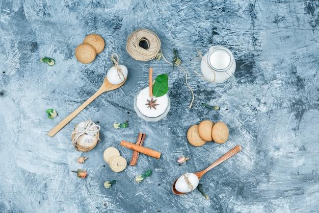 Leg plat een kan melk en een glazen kom yoghurt met lepels, koekjes, eieren, kluwen, kaneel en een plant op een donkerblauw marmeren oppervlak. horizontaal Gratis Foto