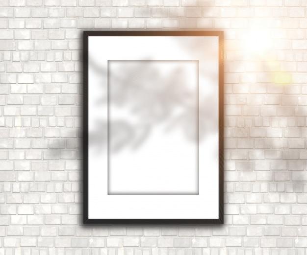 Lege afbeeldingsframe op bakstenen muur met schaduw en zonneschijn Gratis Foto