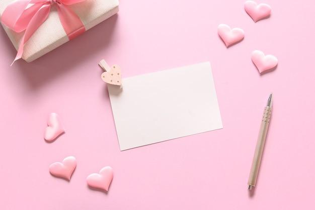 Lege blanco voor valentijn kaart met cadeau en roze romantische harten op roze achtergrond. wenskaart met kopie ruimte. Premium Foto