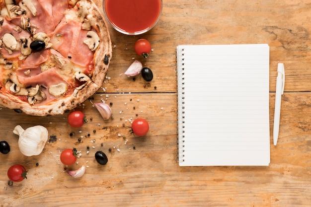 Lege blocnote en pen dichtbij bacandeegwaren met tomatensaus op houten lijst Gratis Foto