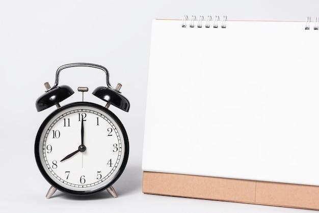 Lege document spiraalvormige kalender voor modelmalplaatje reclame en het brandmerken met klok op grijze achtergrond. Premium Foto