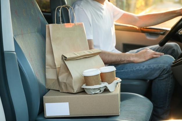 Lege doos, koffiekopjes, papieren verpakkingen en koerier in de auto. levering Premium Foto