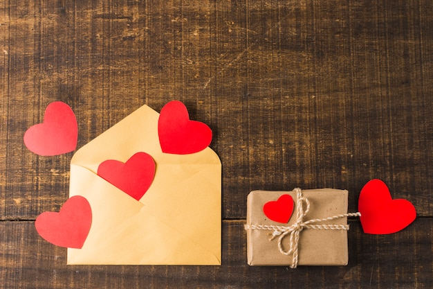 Lege envelop; harten en geschenkdoos omwikkeld met bruin papier gerangschikt over getextureerd oppervlak Gratis Foto