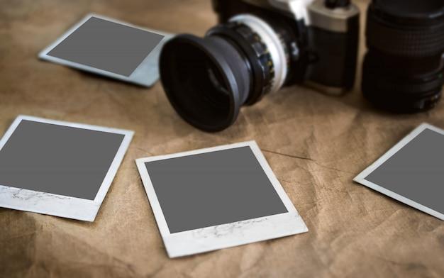 Lege fotokaarten, fotolijst op vintage textuur met geblauwd retro camera, fotografie mockup. Premium Foto