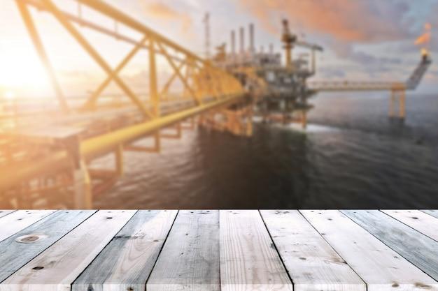 Lege houten plank tafel met olie- en gasplatform of bouwplatform offshore rig wazige achtergrond voor presentatie en advertorial. Premium Foto