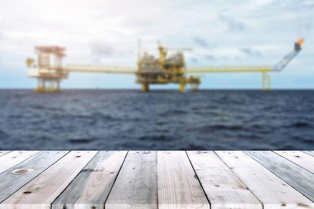Lege houten planklijst met olie en gasplatform of van het de platform onduidelijke installatie van het bouwplatform onduidelijke beeldachtergrond. Premium Foto