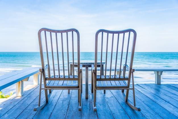 Lege houten stoel en tafel op terras met prachtige tropische strand en zee Gratis Foto