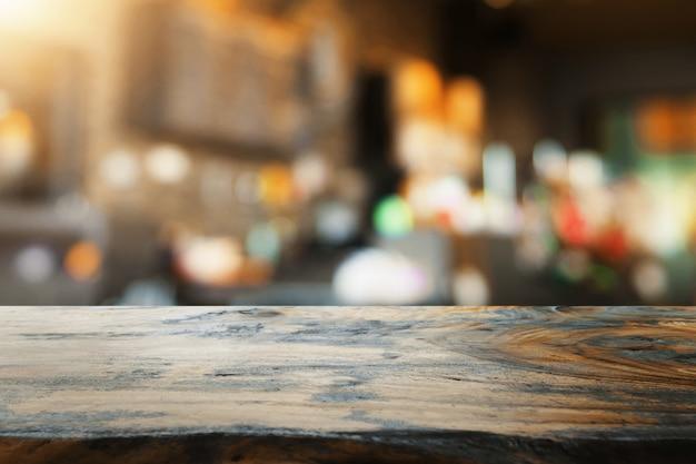 Lege houten tafel en vervagen coffeeshop achtergrond Premium Foto