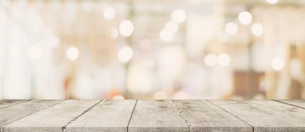 Lege houten tafel en wazig licht tafel in winkelcentrum met bokeh achtergrond. product weergavesjabloon. Premium Foto