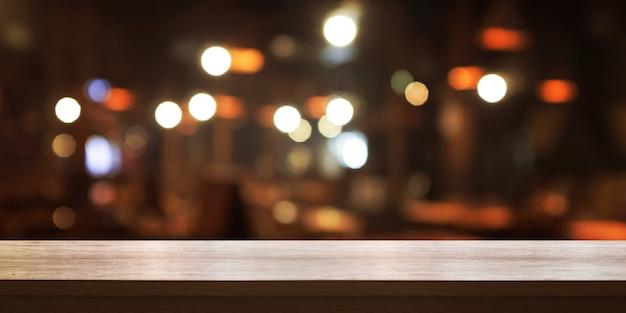 Lege houten tafelblad met vervagen koffieshop of restaurant interieur achtergrond Premium Foto