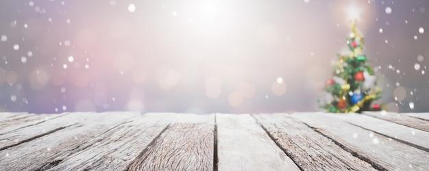 Lege houten tafelblad op onscherpte met bokeh kerstboom banner achtergrond met sneeuwval. Premium Foto