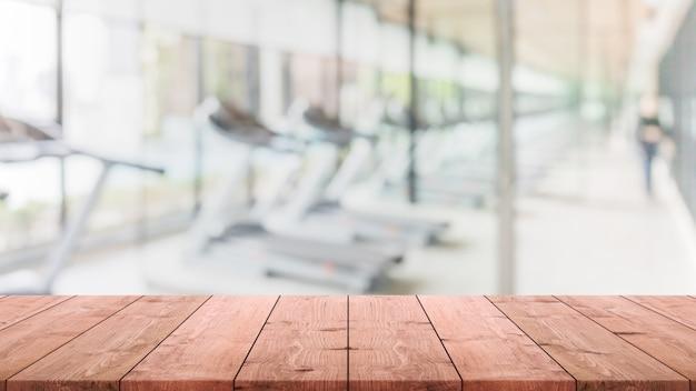 Lege houten tafelblad op wazig met bokeh trainings kamer, fitnees en gym interieur banner achtergrond - kan worden gebruikt voor weergave of montage van uw producten Premium Foto