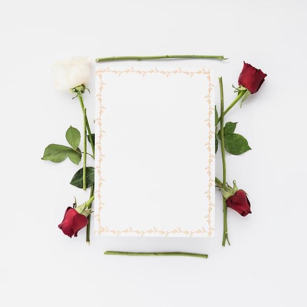 Lege kaart met rode en witte rozen op witte achtergrond Gratis Foto