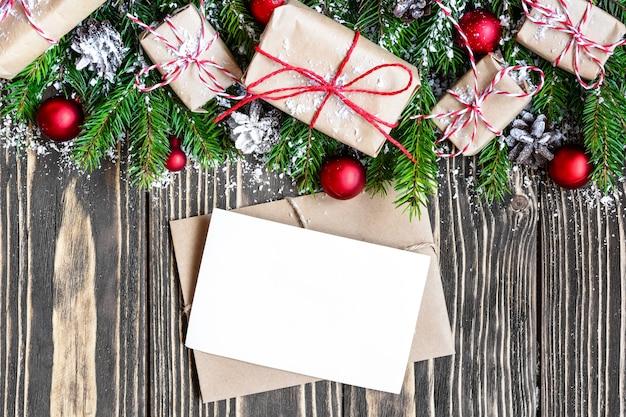 Lege kerst wenskaart en envelop met fir tree takken, geschenkdozen, decoraties en dennenappels Premium Foto