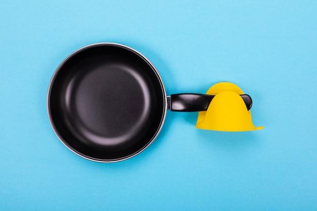 Lege keukenpan met ovenwant die op blauw wordt geïsoleerd Premium Foto