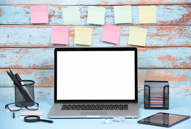 Lege kleurrijke zelfklevende notities tegen houten muur met kantoorbenodigdheden en laptop Gratis Foto