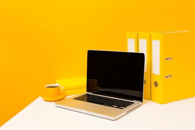 Lege laptop en gele mappen Gratis Foto
