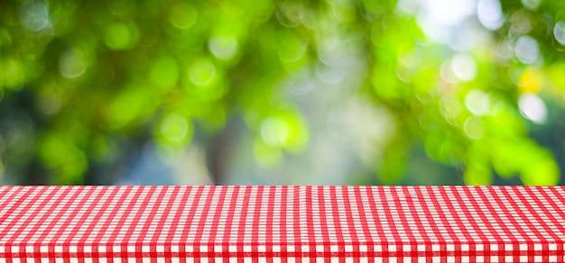 Lege lijst met rood tafelkleed over onduidelijk beeld groene boom en bokeh achtergrond, voor voedsel en product de achtergrond van de vertoningsmontering, banner Premium Foto