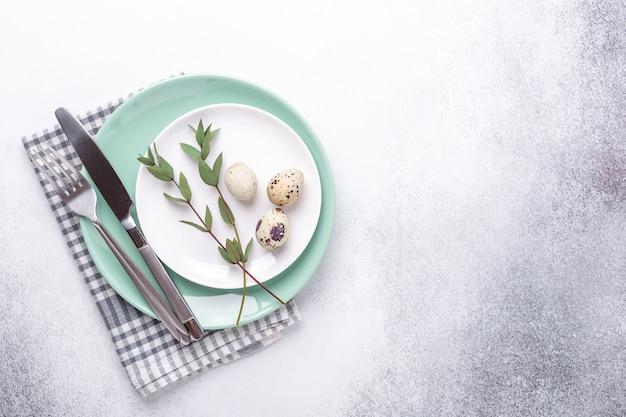 Lege munt en witte borden, linnen servet, eucalyptus bladeren en eieren. pasen tafel instelling Premium Foto