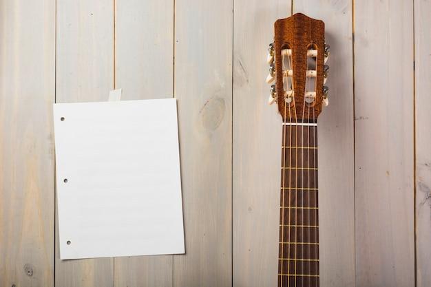 Lege muzikale pagina die op houten muur met het hoofd van de gitaar wordt geplakt Gratis Foto