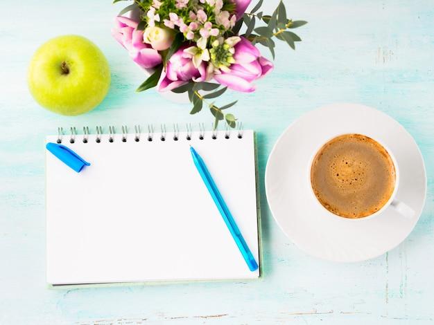 Lege notitieboekjepagina met blauwe pen en kopkoffiebloemen Premium Foto