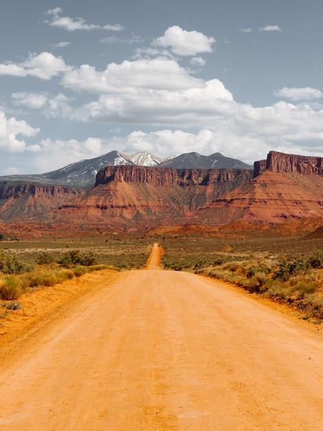 Lege onverharde weg in het midden van droge struiken richting de woestijn Gratis Foto