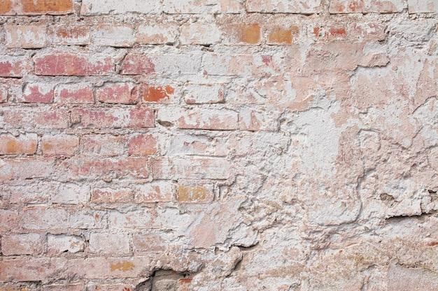 Lege oude bakstenen muur textuur. geschilderde grungy muuroppervlak. grunge rode stonewall achtergrond. shabby gevel van een gebouw met beschadigde pleister. Premium Foto
