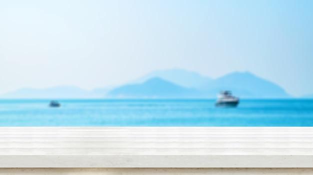 Lege oude donkere houten tafelblad met vervagen blauwe hemel en zee bokeh achtergrond Premium Foto